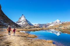 Mother and daughter backpack on Matterhorn mountain, Zermatt, Sw. Mother and daughter backpack on their holiday at Matterhorn mountain with reflection on lake Royalty Free Stock Photos