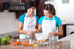 Mother daughter baking. Middle aged mother teaching teen daughter baking in kitchen Royalty Free Stock Photography