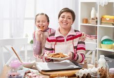 Mother and daughter baking cookies, girl eat cookie, home kitchen interior, healthy food concept Stock Photo