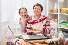 Mother and daughter baking cookies, girl eat cookie, home kitchen interior, healthy food concept Royalty Free Stock Photography