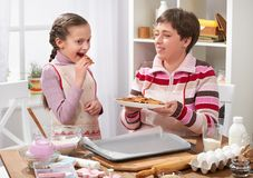 Mother and daughter baking cookies, girl eat cookie, home kitchen interior, healthy food concept Stock Photography