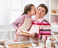 Mother and daughter baking cookies, home kitchen interior, healthy food concept Stock Photography