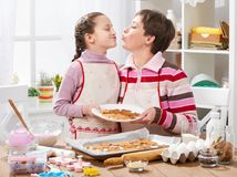 Mother and daughter baking cookies, home kitchen interior, healthy food concept Royalty Free Stock Images