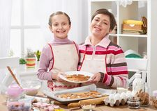 Mother and daughter baking cookies, home kitchen interior, healthy food concept Royalty Free Stock Image