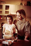 Mother and daughter baking. Mother and daughter baking cookies in kitchen Royalty Free Stock Photography