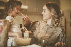 Mother and daughter baking. Mother and daughter baking cookies in kitchen.  Making fun in kitchen Stock Photography