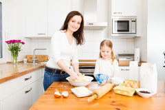 Mother And Daughter Baking Cookies. In their kitchen Stock Photo