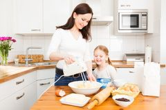 Mother And Daughter Baking Cookies. In their kitchen Royalty Free Stock Image