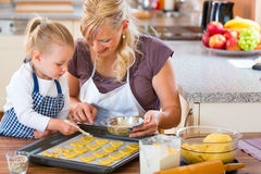 Mother and daughter baking cookies together Stock Photography