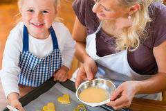 Mother and daughter baking cookies together Stock Image