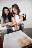 Mother and Daughter Baking Cookies. Young mother with daughter in kitchen preparing cookies stock photo