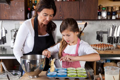 Mother and daughter baking at home stock photos