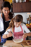 Mother and daughter baking at home Stock Image