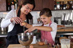 Mother and daughter baking in the kitchen Stock Photos