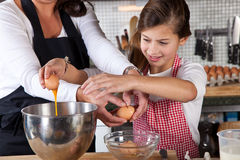 Mother and daughter baking in the kitchen Stock Images