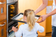 Mother and daughter baking in kitchen. Mother and daughter baking cookies in the oven at home Stock Image