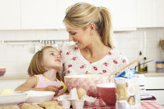 Mother And Daughter Baking In Kitchen Stock Images
