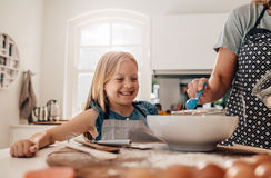 Mother and daughter baking in kitchen. Happy little girl standing in kitchen and her mother cooking food. Mother and happy daughter baking in kitchen Royalty Free Stock Images