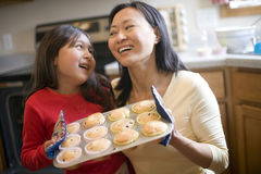 Mother and daughter baking muffins Stock Photos