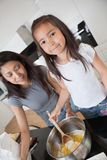 Mother and daughter Baking together. Women and child preparing dough in kitchen stock photo