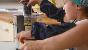 Mother and daughter baking together at home in the kitchen stock video