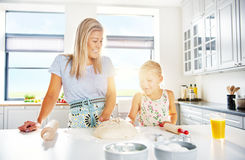 Mother and daughter baking in a white kitchen. Mother and daughter baking in a pristine white kitchen standing working on a mound of dough together backlit by Stock Photography