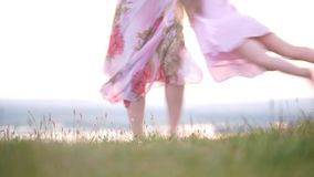 Mother and daughter barefoot legs running having fun on the grass at summer sunset stock video
