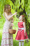 Mother and daughter with a basket of cherries. Mother and daughter in the garden with a basket of cherries Stock Image