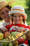 Mother and daughter with basket of fruits Stock Photography