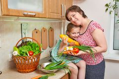 Mother and daughter with basket of vegetables and fresh fruits in kitchen interior. Parent and child. Healthy food concept Royalty Free Stock Image