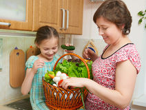 Mother and daughter with basket of vegetables and fresh fruits in kitchen interior. Parent and child. Healthy food concept Stock Image