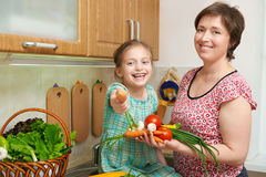Mother and daughter with basket of vegetables and fresh fruits in kitchen interior. Parent and child. Healthy food concept Royalty Free Stock Photo