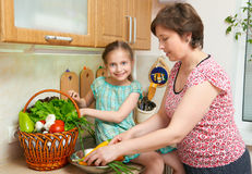 Mother and daughter with basket of vegetables and fresh fruits in kitchen interior. Parent and child. Healthy food concept Stock Photo