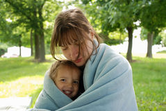 Mother and daughter are basking wrapped in blanket. Mother and daughter wrapped in blanket sit on a bench in early summer morning Royalty Free Stock Image