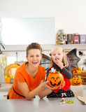 Mother with daughter in bat costume eating halloween candy Royalty Free Stock Photo
