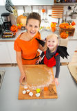 Mother with daughter in bat costume making Halloween cookies Stock Images