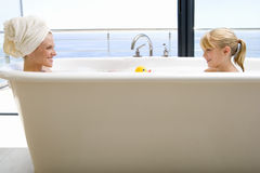 Mother and daughter (6-8) in bath outdoors, smiling at each other, side view Stock Photography