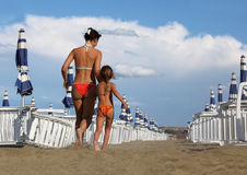 Mother and daughter in bathing suit going on beach. Young mother and  little daughter in bathing suit going on beach. mother holds daughter's hand, rows of white Stock Images