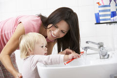 Mother And Daughter In Bathroom Brushing Teeth Royalty Free Stock Photos
