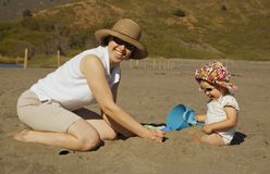 Mother and daughter on the bea. A young attractive mother looks up from playing with her toddler daughter in the sand on the beach (shot in San Francisco Bay Royalty Free Stock Photo