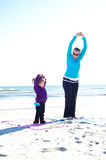 Mother and daughter at the beach. Mother and baby doing yoga at the beach Stock Images