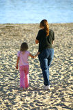 Mother and Daughter on Beach. A mother and daughter stroll toward the water on the edge of Monterey Bay. The sand is churned from hundreds of beachgoers before royalty free stock photography