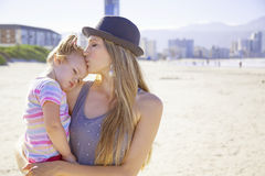 Mother and daughter on beach. Hugging and kissing Royalty Free Stock Images