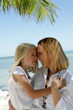 Mother and daughter on beach. Mother cuddling daughter on tropical beach Stock Image