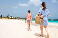 Mother and daughter at beach. Back view family mother and daughter walking at beach in Barbados enjoying tropical summer vacation royalty free stock images