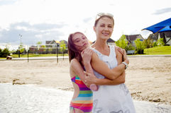 Mother and daughter at the beach embracing Stock Image