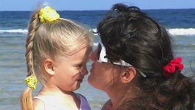 Mother and daughter at beach. Happy family mother and daughter at beach kissing stock video footage