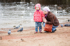 Mother and daughter on beach, looking at birds. Mother and daughter together on beach by fall, looking at birds Royalty Free Stock Images