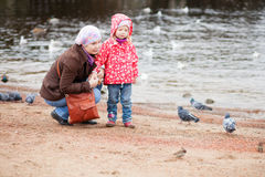 Mother and daughter on beach, looking at birds Royalty Free Stock Image