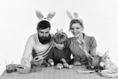 Mother, daughter and bearded father with happy faces painting eggs. Mother, daughter and bearded father with happy faces painting colorful eggs. Holiday spirit royalty free stock photo